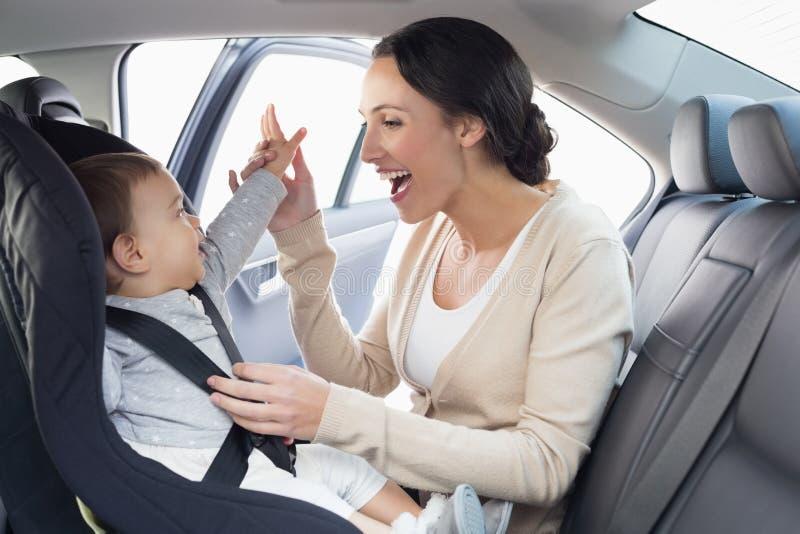 Macierzysty zabezpieczać jej dziecka w samochodowym siedzeniu zdjęcie stock