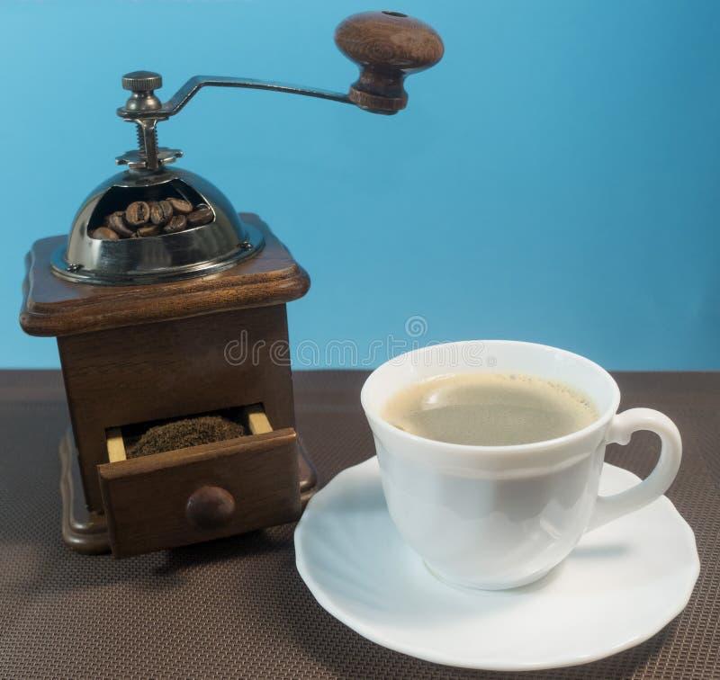 Macinacaffè con la tazza di caffè su fondo blu fotografia stock libera da diritti