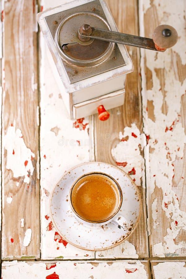 Macinacaffè d'annata e caffè in una tazza su una vecchia tavola di legno immagini stock libere da diritti