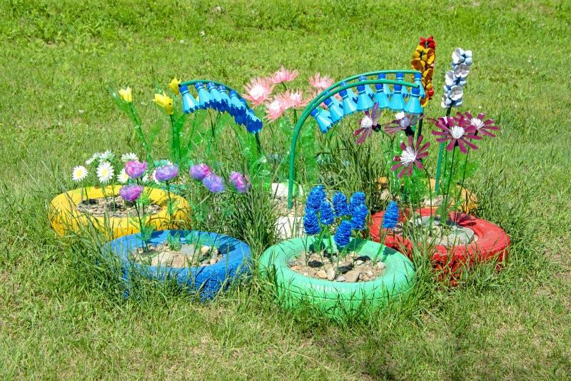 Macizo de flores con las flores hechas de las botellas plásticas viejas fotos de archivo libres de regalías