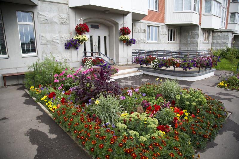 Macizo de flores de las flores brillantes de diversas plantas delante de la casa Agricultura fotos de archivo libres de regalías