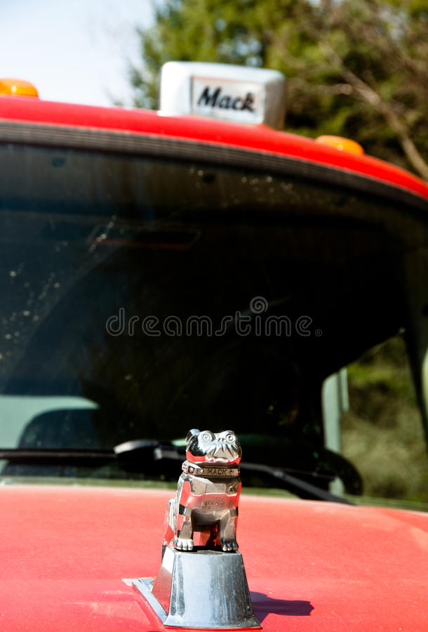Mack bulldog on an old red truck stock images
