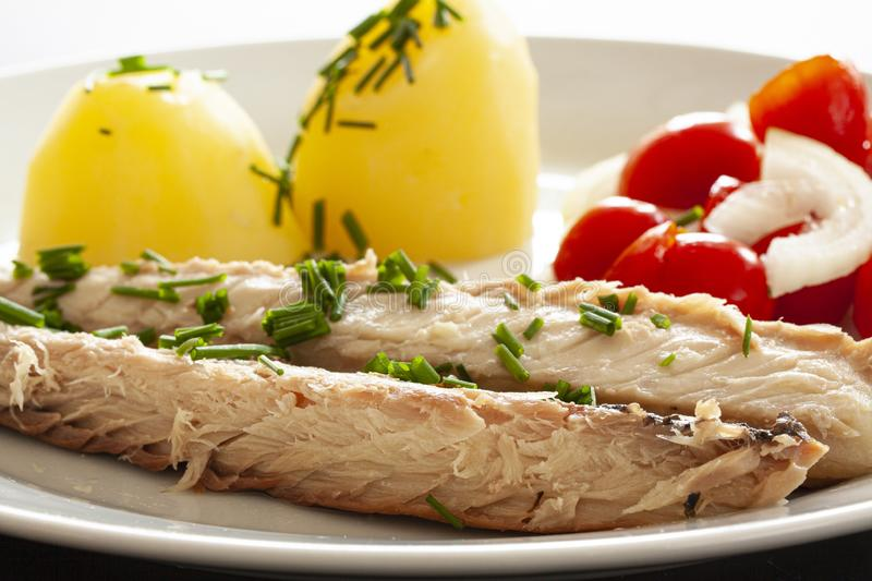 Mackerel fish dish with potatoes, chives and tomato salad. Fatty, oily fish is an excellent and healthy source of DHA and EPA, whi. Ch are two key types of omega stock image