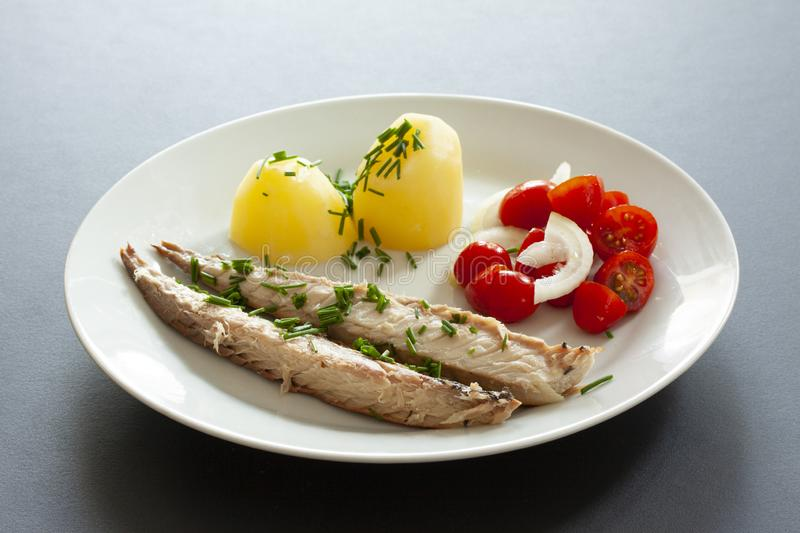 Mackerel fish dish with potatoes, chives and tomato salad. Fatty, oily fish is an excellent and healthy source of DHA and EPA, whi. Ch are two key types of omega royalty free stock photo