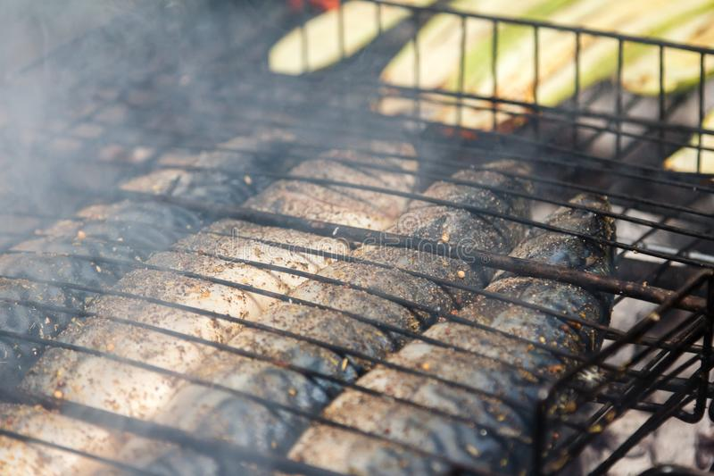 Mackerel fish roast on grill barbecue with vegetables, bonfire coals with fire, stock photography