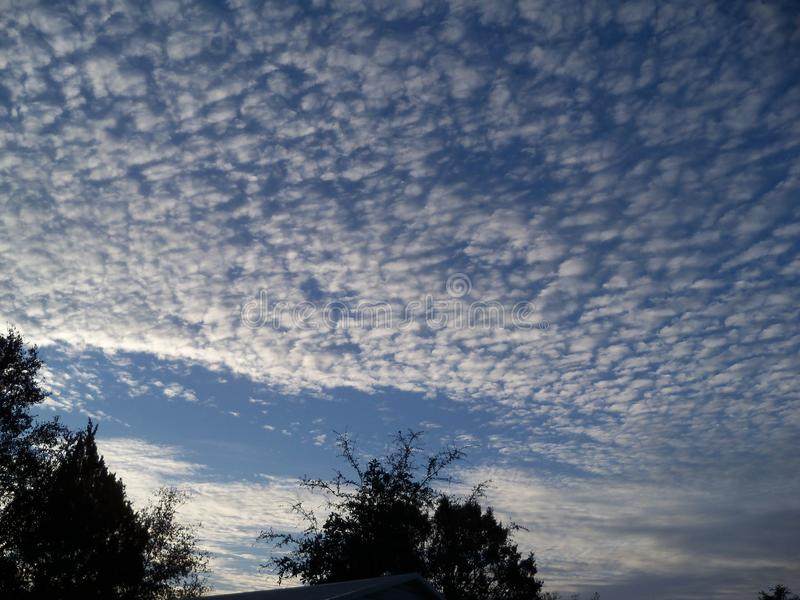Mackerel sky in the morning. Looking South towards a sun beginning to rise and a mackerel sky stock image