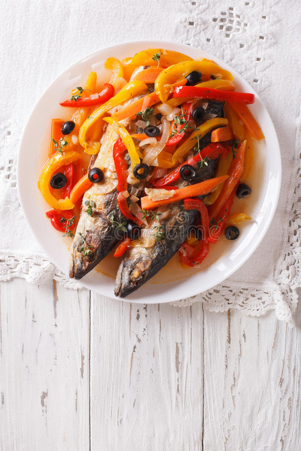 Mackerel in vegetable marinade close-up on the table. vertical t. Mackerel in vegetable marinade close-up on a plate on the table. vertical view from above stock photo