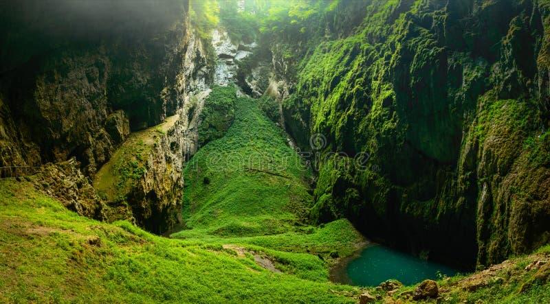Macocha avgrund, Moravian Karstmicroclimate med saftig grönska och en liten sjö royaltyfria bilder