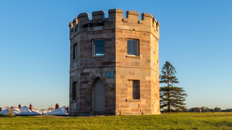 Macquarie Watch Tower at Sunrise. Morning glow of the sun lighting up behind the historic Macquarie Watch Tower in Sydney, Australia stock photo