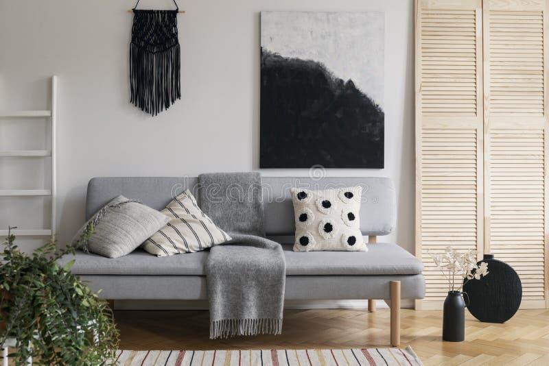 Macramê feito a mão preto e pintura extravagante na parede branca de sala de visitas sofisticada interior com o sofá elegante cin imagem de stock