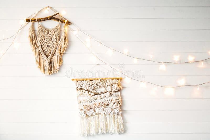 Macrame hanging on white wooden wall with lights. Stylish boho decor, modern wall hanging. Modern interior decor in scandinavian stock image