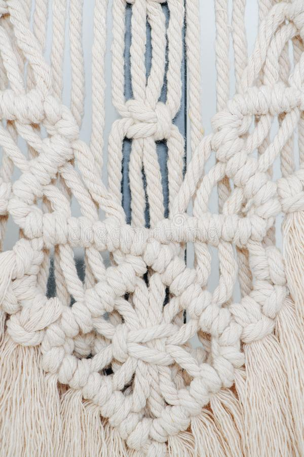 Macrame tapestry up close. Knots, ropes and tassels arranged in a pattern. Whitish macrame tapestry up close. Knots, ropes and tassels arranged in a pattern as a stock photos