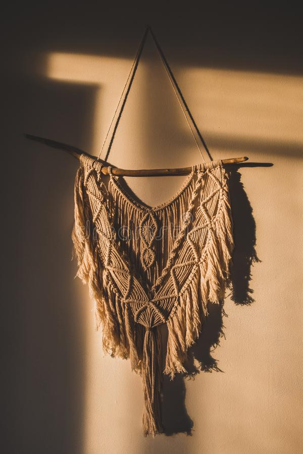 Macrame wall hanging in the sunny spot of the room. stock image