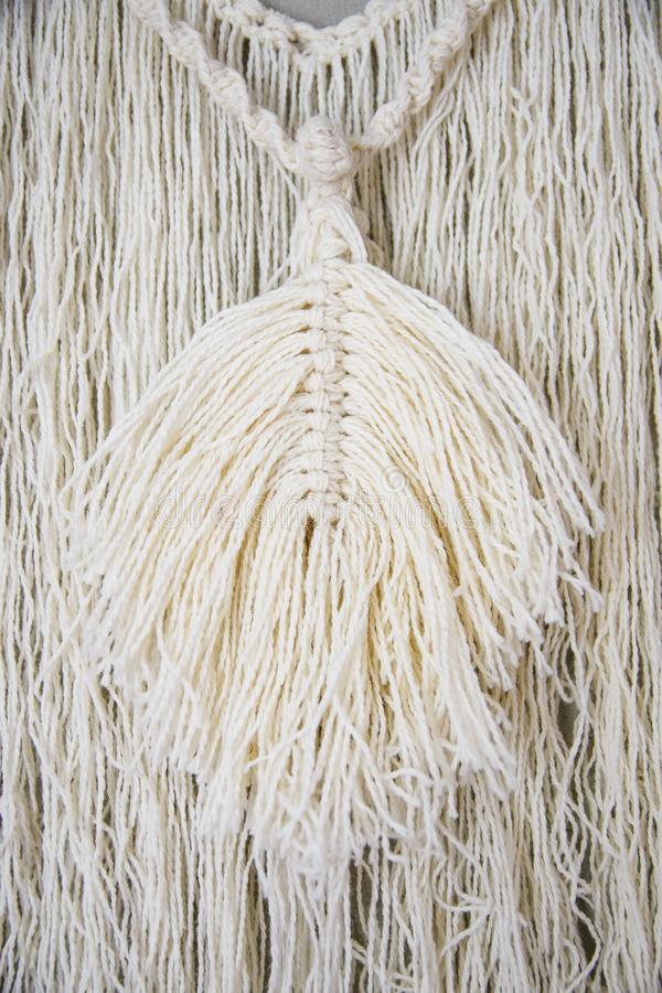 Macrame Wall Hanging. Wall panel in the style of Boho made of cotton threads in natural color using the macrame technique for home decor and wedding decoration royalty free stock image