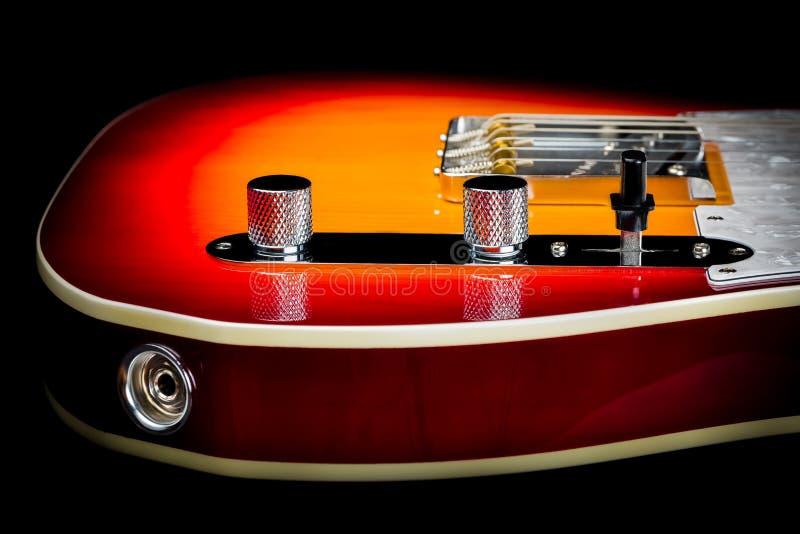Macro étroit d'un corps de guitare électrique avec des boutons de volume et de ton comme foyer principal image stock