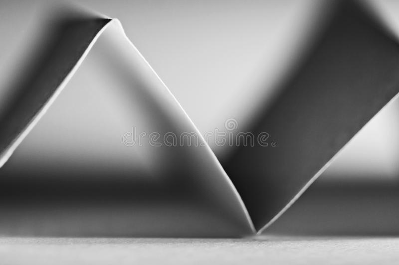 Macro, abstract, black and white picture of a zig-zag paper. On paper background royalty free stock image