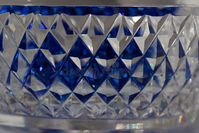 Macro abstract texture background of beautiful hand cut lead crystal glass with diamond cut facets. Reflecting brilliant blue color stock photos