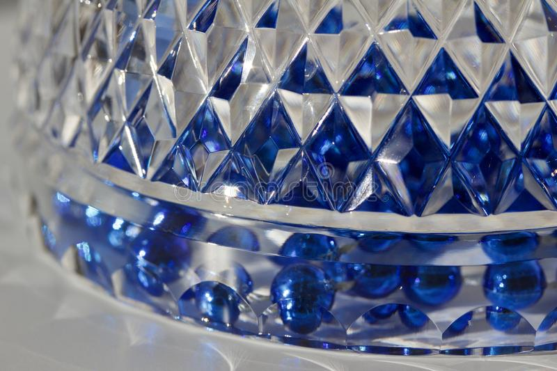 Macro abstract texture background of beautiful hand cut lead crystal glass with diamond cut facets. Reflecting brilliant blue color royalty free stock images