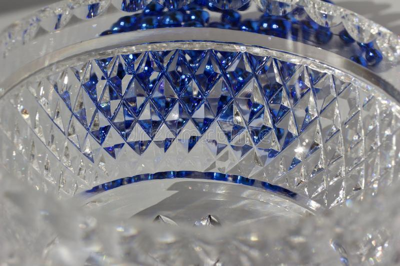 Macro abstract texture background of beautiful hand cut lead crystal glass with diamond cut facets. Reflecting brilliant shimmer and blue color stock image