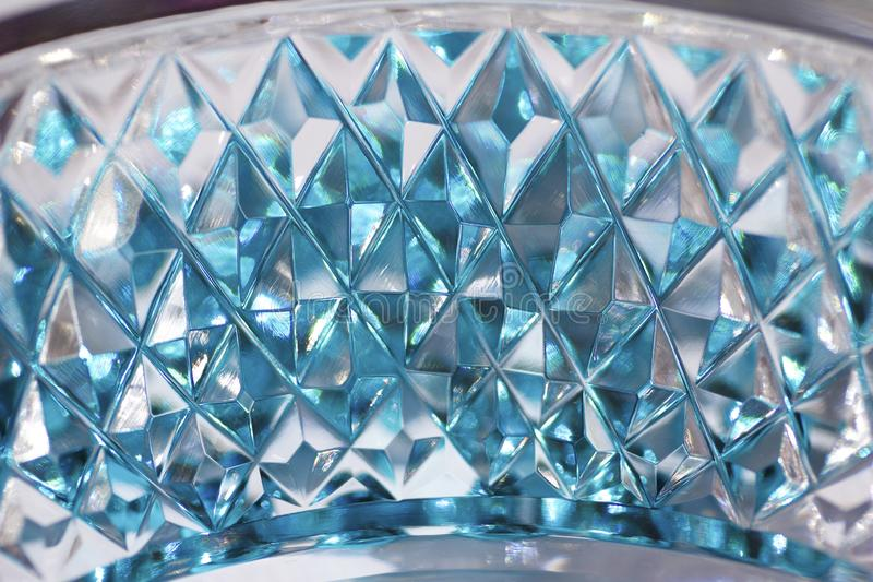 Macro abstract texture background of beautiful hand cut lead crystal glass with diamond cut facets. Reflecting brilliant sky blue color stock photo
