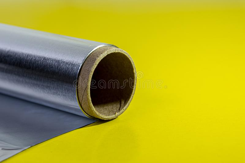 Macro aluminum foil for baking and baking. Food foil roll, side view. Packaging foil on a yellow background. Kitchen utensils for royalty free stock photos