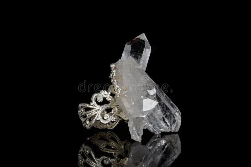 Macro anneau argenté avec un crystalon minéral de roche un fond noir photos stock
