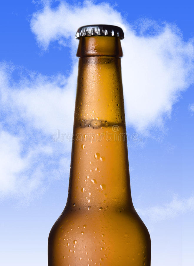 Macro beer golden bottle neck with frost and bubbles in brown glass on blue sky royalty free stock image