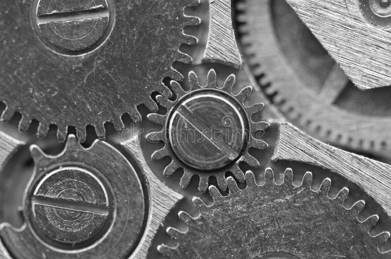 Macro. Black and white background. Metal close-up background of. An old clock mechanism of cogwheels. Conceptual photo for your successful business design or royalty free stock photos