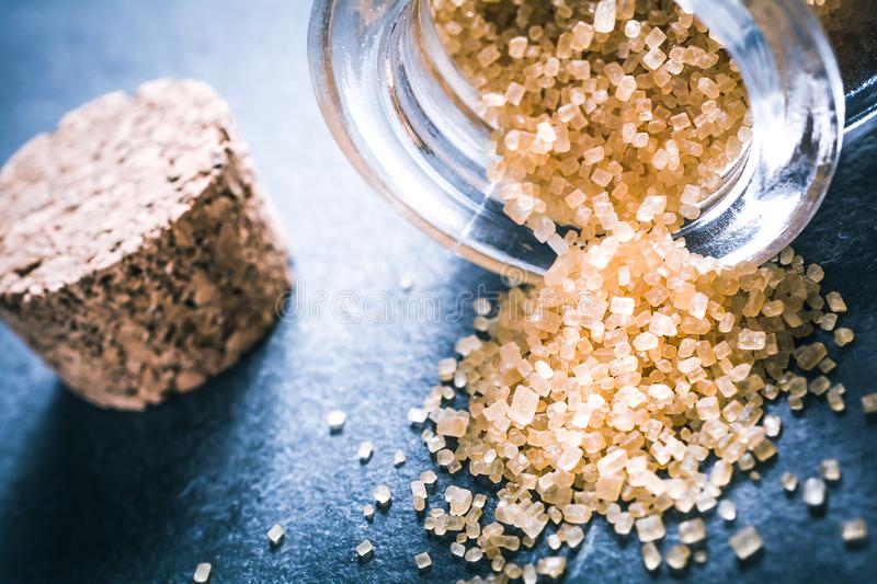 Macro Of Brown Raw Sugar Spilled Out Of An Overturned Glass Bottle Next To A Cork Stopper On Slate Stone. A Macro Of Brown Raw Sugar Spilled Out Of An Overturned royalty free stock photo