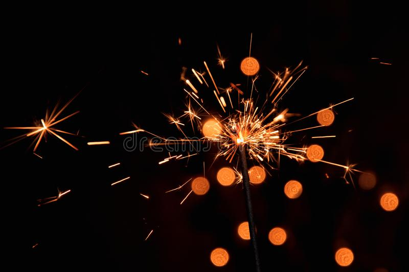 Macro, close up. Bright burning sparkler with flying sparks. Dark background with blurred lights of Christmas garland. royalty free stock image