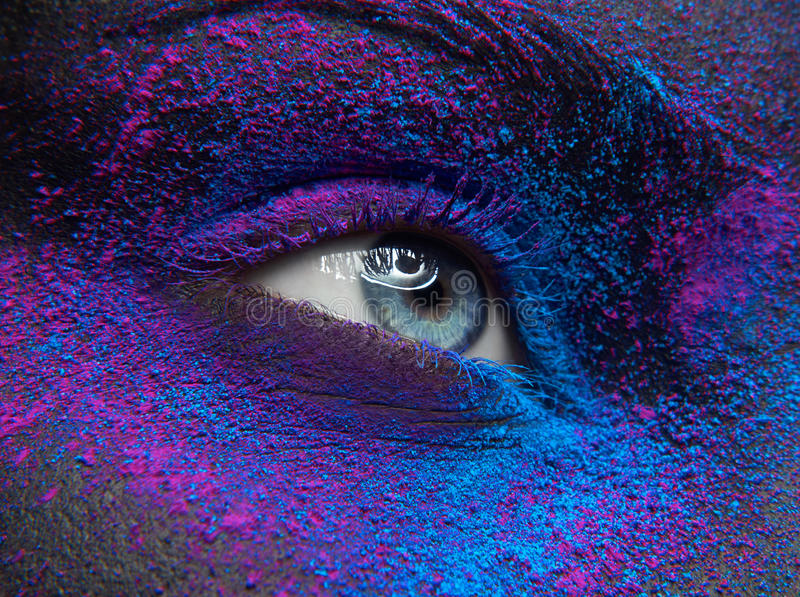 Macro and close-up creative make-up theme: Beautiful female eye with dry paint dust pigment on face, purple and blue color. Art royalty free stock photo