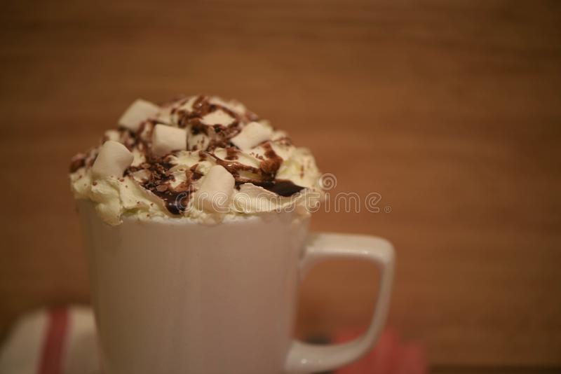 Macro close up food photography image of hot chocolate drink in a mug with cream sauce and marshmallows on rustic blur background stock photo