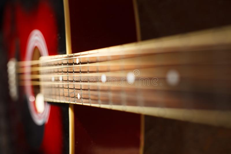 Macro close up view of a Part of a red acoustic guitar on black backgroun with a small Depth of field stock photos