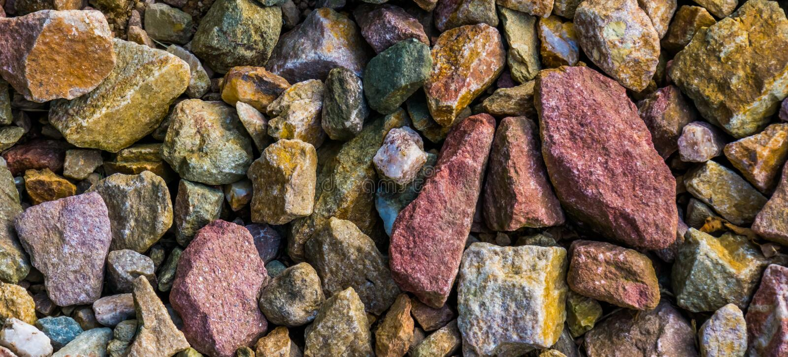 Macro closeup of gravel stones in diverse colors, rock pattern background. A macro closeup of gravel stones in diverse colors, rock pattern background royalty free stock photo