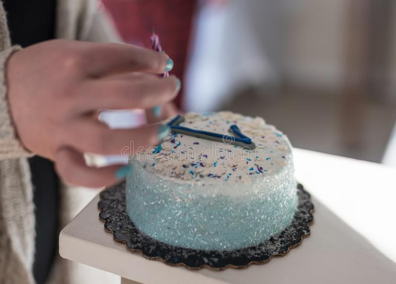 Closeup Of Woman Placing Candle On Birthday Cake With Number One
