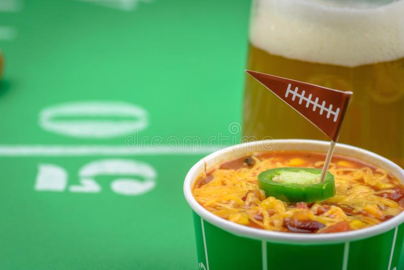 Closeup of a small bowl of chili and beer mug on table decorated. Macro closeup of small bowl of chili and beer mug on table decorated for big football game royalty free stock images