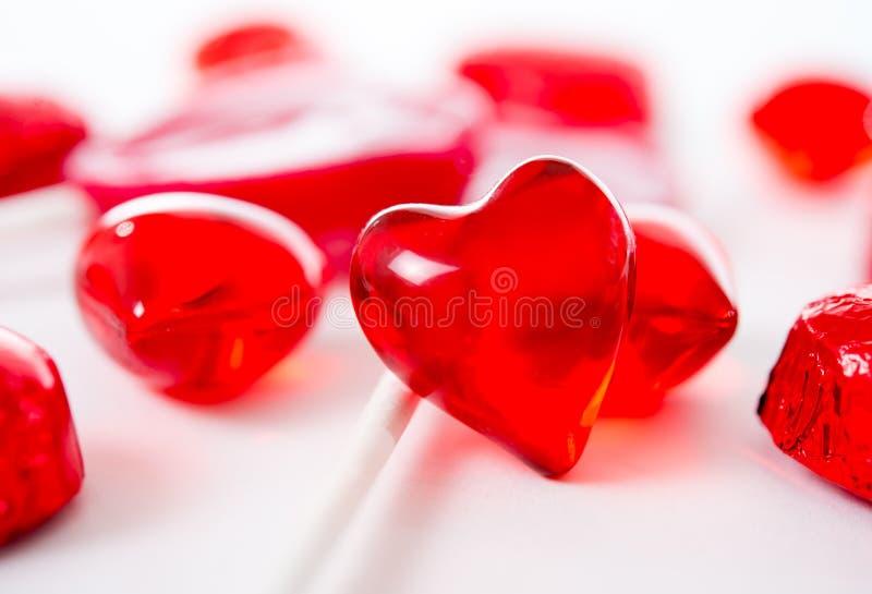 Macro coeur rouge avec des chocolats et des lucettes sur le fond blanc photographie stock