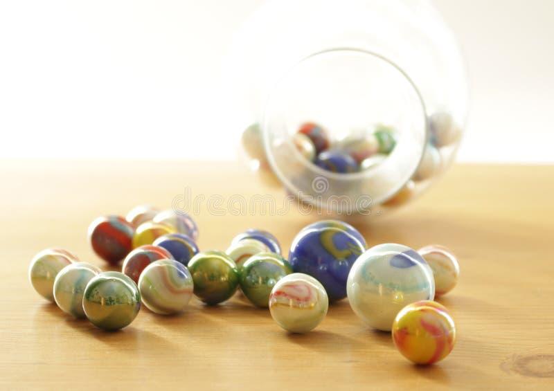 Macro colorido dos mármores na tabela com mármores borrados no fundo, fotos de stock royalty free
