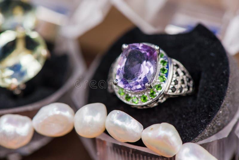 Macro colpo dell'anello di fidanzamento d'argento in contenitore di regalo su fondo variopinto e scintillante immagini stock libere da diritti