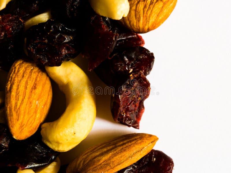 Macro colpo delle mandorle, delle arachidi, degli anacardi e dei mirtilli rossi secchi su fondo bianco con spazio per lo spazio d immagini stock libere da diritti