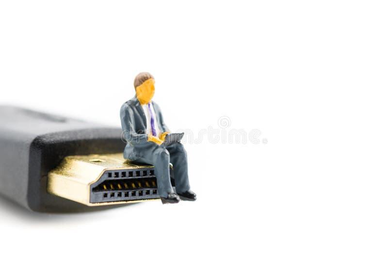 Macro colpo sulla figura miniatura come uomo di affari che lavora al taccuino del computer portatile che si siede sulla spina di  fotografia stock libera da diritti