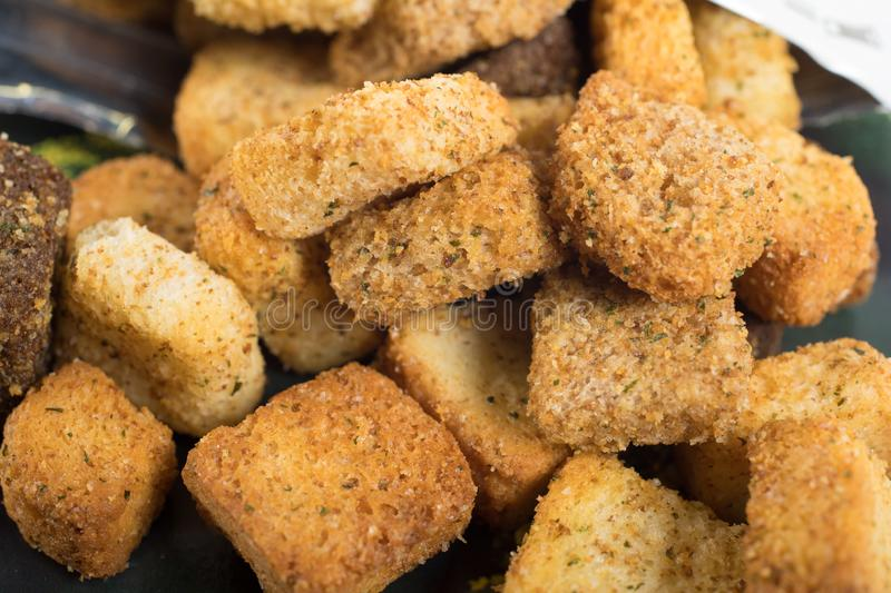 Macro of croutons. Closeup of croûtons. Croutons is a piece of sautéed or rebaked bread, often cubed and seasoned, that is used to add texture and flavor royalty free stock images