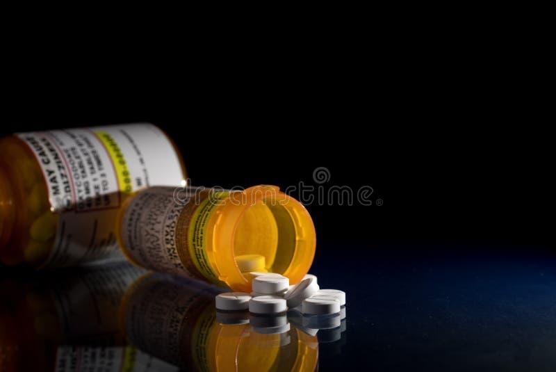 Macro de tabuletas do opiáceo do oxycodone com as garrafas da prescrição contra o fundo escuro imagem de stock