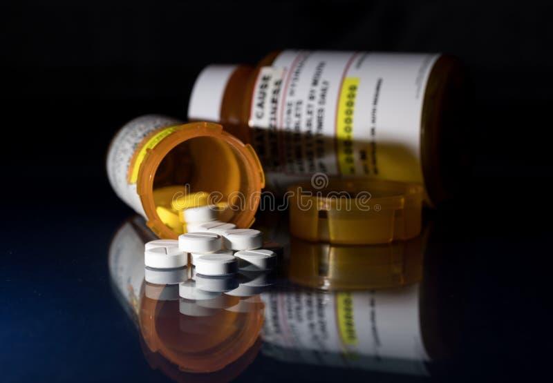 Macro de tabuletas do opiáceo do oxycodone com as garrafas da prescrição contra o fundo escuro imagens de stock royalty free