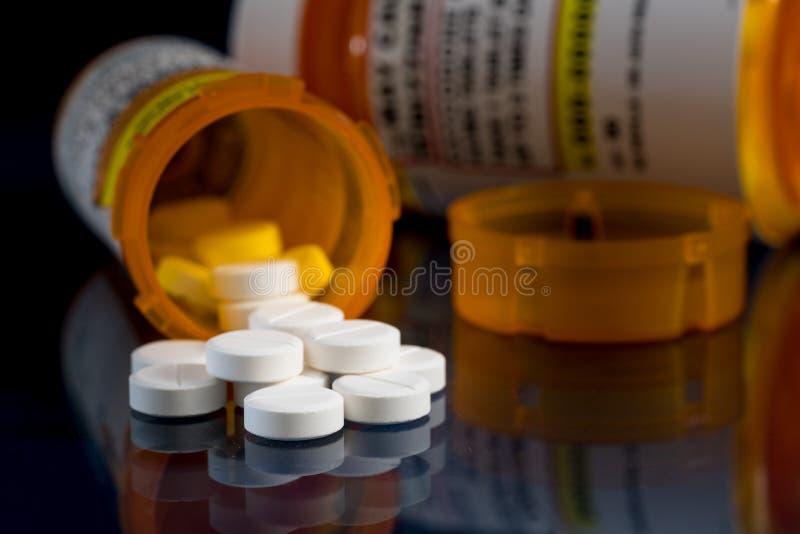 Macro de tabuletas do opiáceo do oxycodone com as garrafas da prescrição contra o fundo escuro imagem de stock royalty free