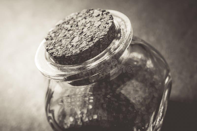 Macro de um Brown Sugar In cru uma garrafa de vidro pequena fechado com Cork Stopper On Slate Stone em cores monocromáticas fotos de stock