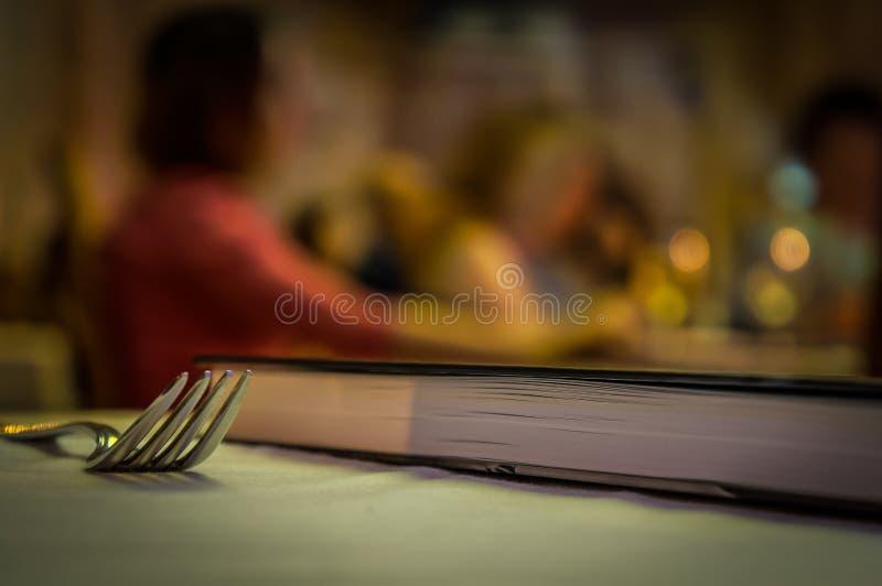 Macro de uma forquilha na tabela com um livro imagem de stock royalty free