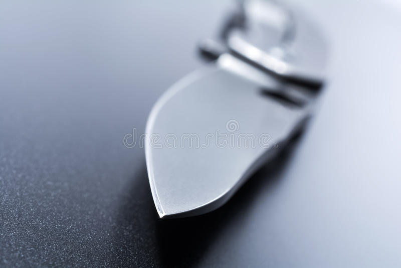 Macro de un punto del cuchillo de un cuchillo militar abierto que está mintiendo en la tierra oscura imagenes de archivo