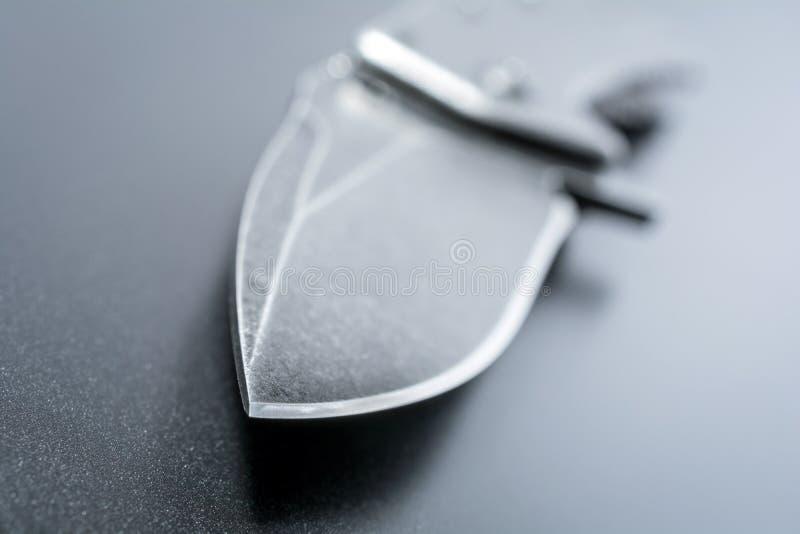 Macro de un punto del cuchillo de un cuchillo plegable negro abierto que está mintiendo en la tierra oscura fotos de archivo