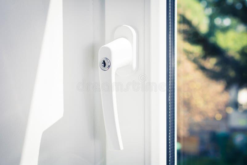 Macro de una manija de ventana bloqueable de una ventana blanca cerrada con los árboles en fondo imagen de archivo